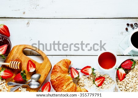 Delicious rural breakfast with oats, fresh strawberries, cup of coffee, fruity jam, honey and croissant on rustic white wooden background with space for text. Top view. Diet or healthy concept. - stock photo
