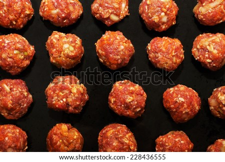 Delicious rustic famous raw meat balls with carrot and onion on the tray just before they go to the oven - stock photo
