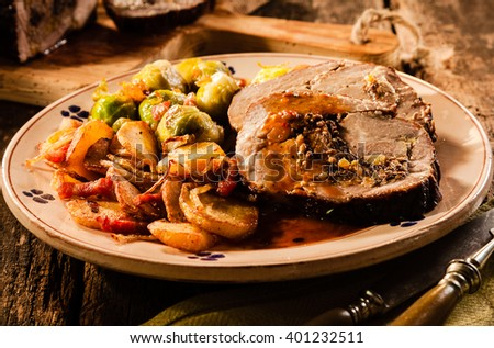 Delicious rustic roast slice menu on wooden table and vintage plate with vegetables. Whole meal with tasty potatoes for restaurant concepts - stock photo