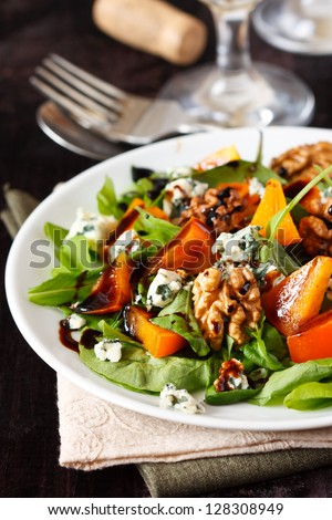Delicious salad. Fresh arugula, persimmon, blue cheese and walnuts with balsamic vinegar. - stock photo