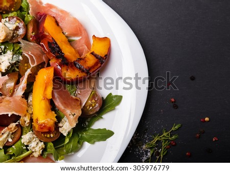 Delicious salad with grilled peaches, prosciutto and cheese in white plate on black board top view - stock photo