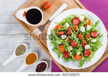 Delicious salad with tomatoes, mini mozzarella, arugula, fried sausages on a white dish, caramelized balsamic vinegar in a gravy boat on a cutting board, studio light, close-up, top view - stock photo