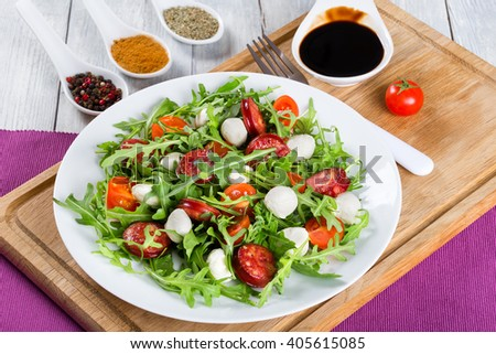 Delicious salad with tomatoes, mini mozzarella, arugula, fried sausages on a white dish on a white rustic table, caramelized balsamic vinegar in a gravy boat. close-up, top view - stock photo