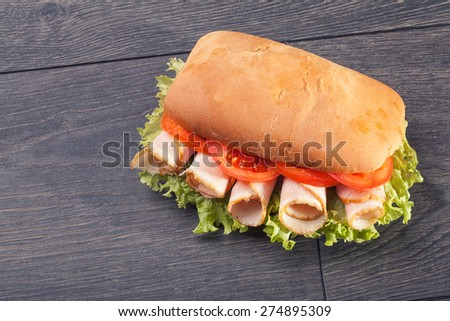 Delicious salami and ham baguettes with fresh lettuce and basil on an old wooden kitchen table top - stock photo