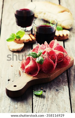 Delicious salami with basil and wine, selective focus and toned image - stock photo