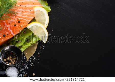Delicious salmon fillet, rich in omega 3 oil, aromatic spices and lemon on fresh lettuce leaves on black wooden background. Healthy food, diet and cooking background with copy space. Top view. - stock photo