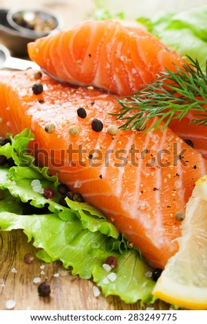 Delicious salmon fillet, rich in omega 3 oil, aromatic spices and lemon on fresh lettuce leaves on rustic wooden background. Healthy food, diet and cooking concept. - stock photo
