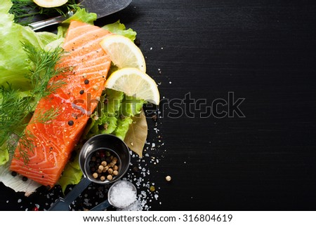 Delicious salmon fillet, rich in omega 3 oil, aromatic spices and lemon on fresh lettuce leaves on black background. Healthy food, diet and cooking background with copy space.  - stock photo