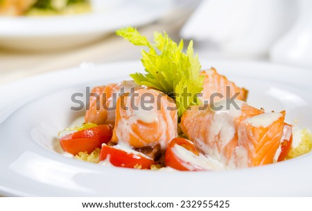 Delicious salmon salad with bite sized pieces of grilled fish fillet served with tomato and lettuce and drizzled with a creamy salad dressing, close up view on a plate - stock photo