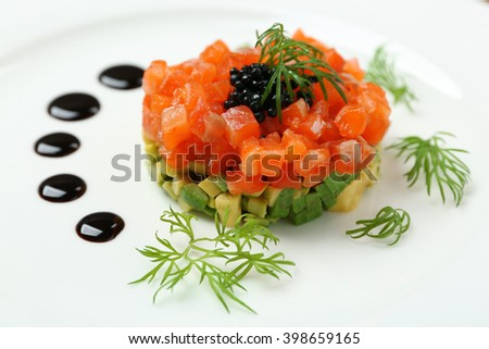 Delicious salmon tartare with black caviar on white plate - stock photo