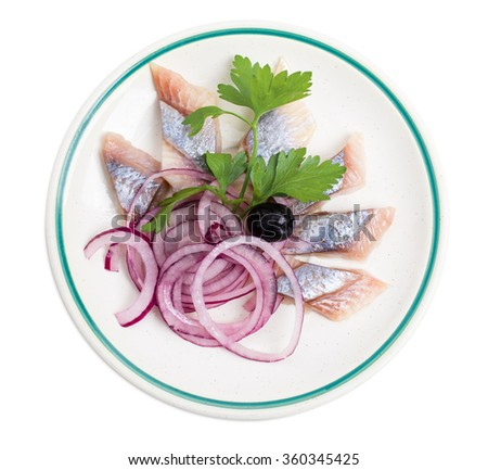 Delicious salted herring with sliced red onion and fresh parsley. Isolated on a white background. - stock photo