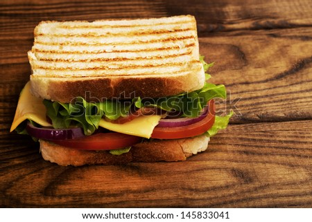 Delicious sandwich stacked high with a juicy ham , cheese, fresh lettuce, onion and tomato on a fresh bun with  standing on  wooden table  - stock photo