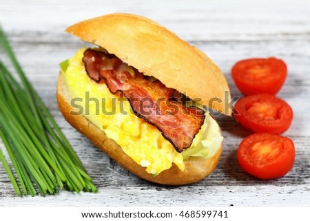 Delicious sandwich with bacon, scrambled egg and lettuce decorated with chives and tomatoes on a wooden table.