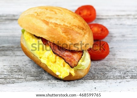Delicious sandwich with bacon, scrambled egg and lettuce decorated with tomatoes on a wooden table.