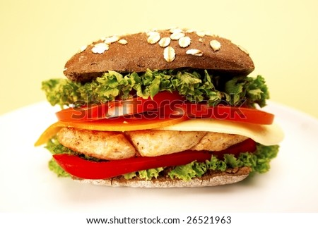 delicious sandwich with chicken, fresh salad, tomato, red paprika and cheese