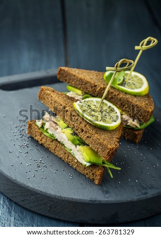 Delicious sandwiches dark bread on skewers with avocado, chicken, dressing, arugula and poppy seeds on a dark background. selective Focus - stock photo