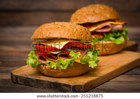 Delicious sandwiches with ham, cheese, tomato and lettuce on the table close up - stock photo