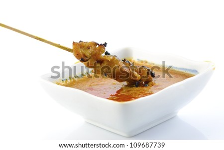 Delicious Satay chicken and peanut sauce over white background - stock photo
