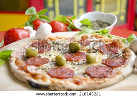 Delicious sausage pizza from wooden oven with fresh tomatoes and olives shallow depth of field - stock photo