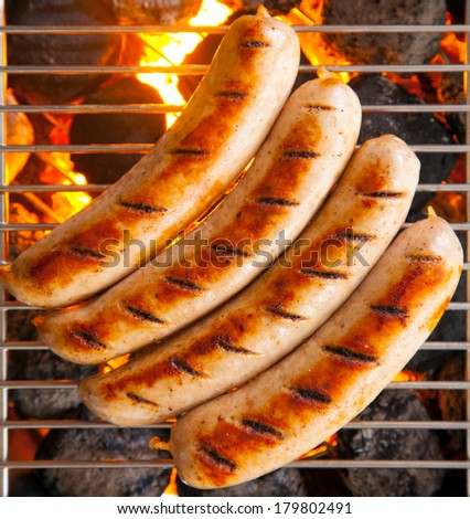 Delicious sausages called bratwurst, on a metal grid grilling over hot coals on a BBQ for a picnic lunch on a summer vacation - stock photo
