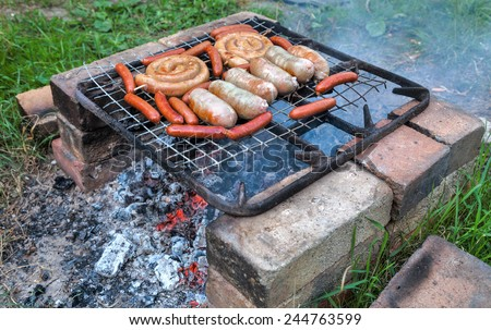 Delicious sausages on a metal grid grilling over hot coals for a picnic lunch on a summer vacation - stock photo