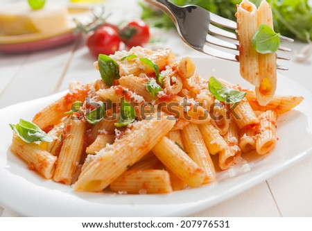Delicious savory Italian penne rigate pasta with fresh basil and grated parmesan cheese served with a salad with a fork with two pasta tubes suspended above the plate - stock photo