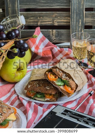 Delicious savory salad sandwiches served on a red and white checked tablecloth for a healthy outdoors summer picnic - stock photo