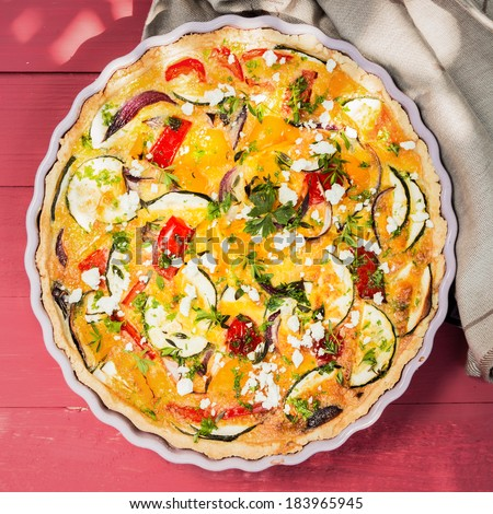 Delicious savory tart or quiche  with eggplant, pepper, tomato and cheese sprinkled with fresh chopped herbs, overhead view - stock photo