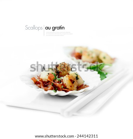 Delicious scallops au gratin starter dish against a white background served with watercress salad, Parmesan cheese and chorizo sausage. Copy space. - stock photo