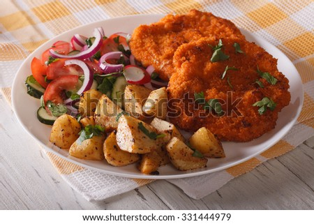 Delicious schnitzel, fried potatoes and vegetable salad on the table close-up. horizontal - stock photo