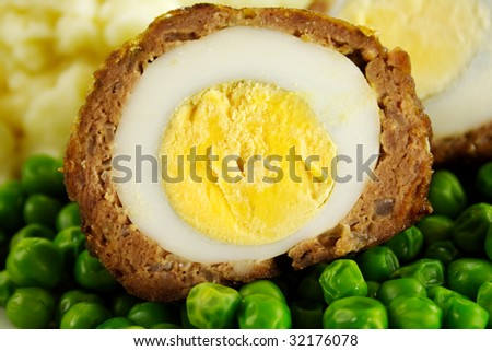 Delicious scotch egg with peas, carrots and mashed potato. - stock photo