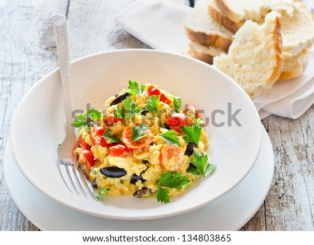 Delicious scrambled eggs with fresh tomatoes olives and parsley leaves breakfast - stock photo
