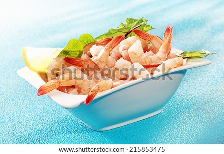 Delicious seafood appetizer of grilled shrimp or pink prawns served in a dish with a slice of lemon and salad greens on a turquoise blue background - stock photo