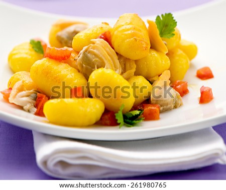 Delicious seafood meal of tradition Italian gnocchi dumplings with clams and tomato garnished with fresh coriander - stock photo