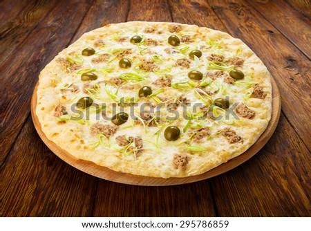 Delicious seafood pizza with tuna fish, olives and leek - thin pastry crust at wooden table background  on wooden desk - stock photo