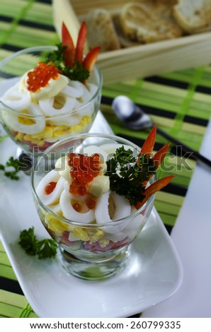 Delicious seafood salad in a glass with calamari and red caviar