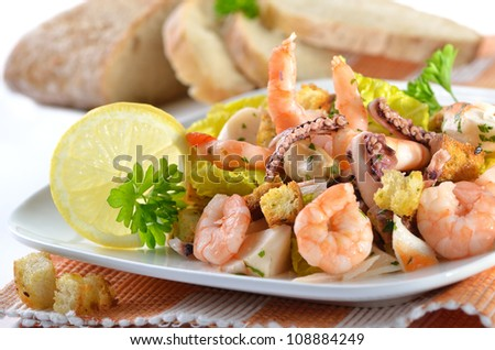 Delicious seafood salad with baked croutons, Italian ciabatta bread in the background - stock photo