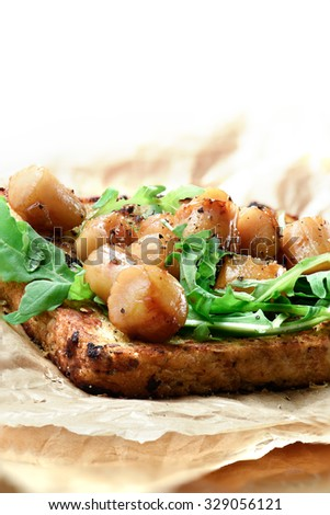 Delicious seafood scallops, poached in white wine with a rocket leaf salad on granary sliced loaf. A culinary treat for any fine cuisine connoisseur. Accommodation for copy space. - stock photo