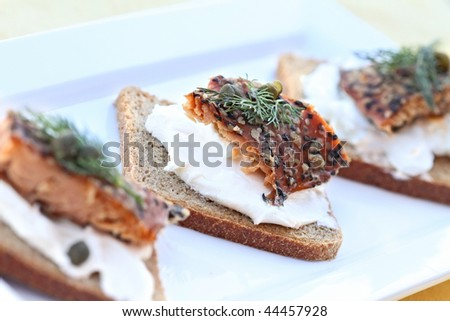 Delicious seasoned smoked salmon with dill and capers served on rye. - stock photo