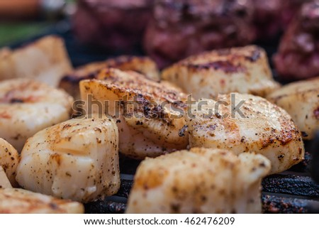Delicious sizzling sea scallops grilling on a charcoal hibachi grill