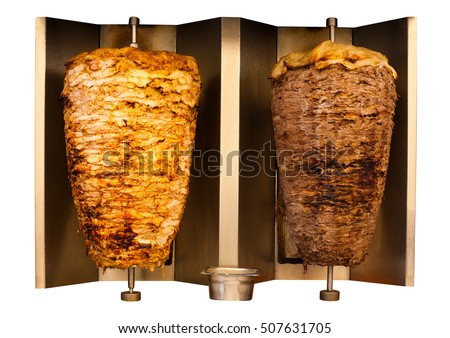 Delicious skewered fast food chicken and lamb mutton kebab, shawarma meat cooking and turning side by side on rotating spit Arab Middle Eastern or Mediterranean style.  Isolated on white background