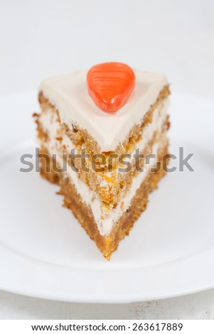 Delicious slice of carrot sponge cake with cream and walnut on white dish - stock photo