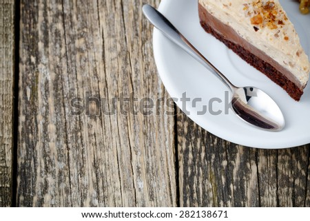 Delicious slice of nuts cake on wooden background.