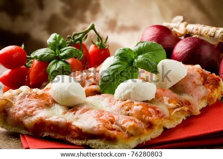 delicious slice of pizza with buffalo mozzarella on wooden table - stock photo