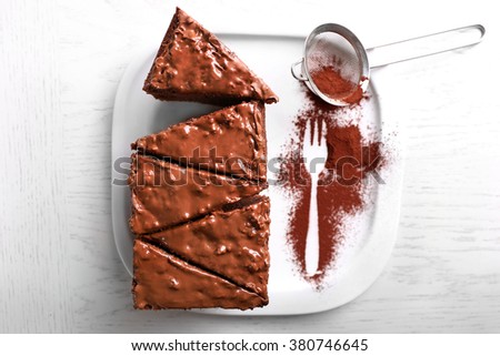 Delicious sliced chocolate cake with nut cream on white plate, close up - stock photo