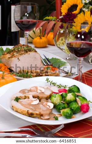 Delicious sliced garlic thyme roast pork loin with mushrooms sauce, brussels sprouts, almonds and radish ready for dinner in middle of fall arrangement table and two glasses of red wine.