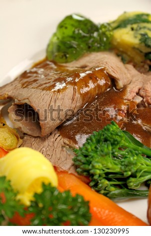 Delicious sliced roast lamb with baked vegetables and mint jelly. - stock photo