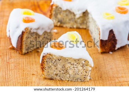 Delicious slices of lemon and almond drizzle cake with poppy seeds and white icing on a wooden board
