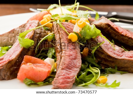 delicious slices of meat with rocket salad and toamto