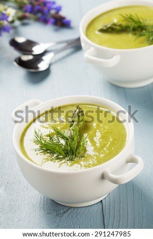 Delicious soup with asparagus, served in white bowls.